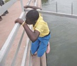 Twelve-year-old Lucky Sappah of the Weija Presby Junior High School perilously working his way over the metal fence of the Weija Dam at 6.17 a.m. Wednesday.